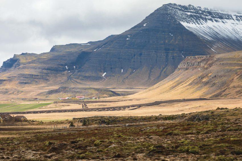 Farm vor einer steilen Bergwand